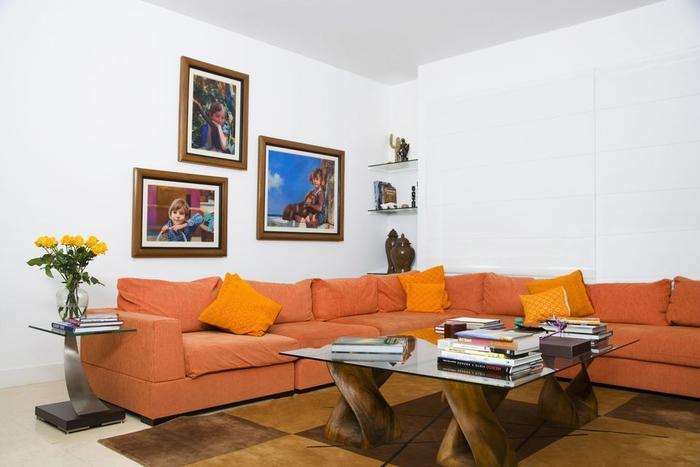 un intérieur blanc rendy plus dynamique grâce au canapé couleur sienne orangé et le mur en cadres
