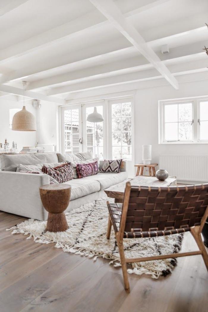 salon bohème chic en blanc aux accents déco ethnique chic, grand canapé blanc associé à des coussins ethniques , tapis berbère stylisé