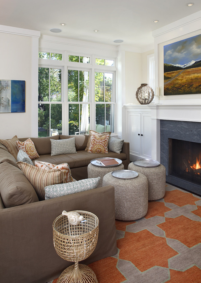 petit salon blanc au design classique, déco aux couleurs terre, tapis en beige et couleur sienne assorti avec les coussins décoratifs