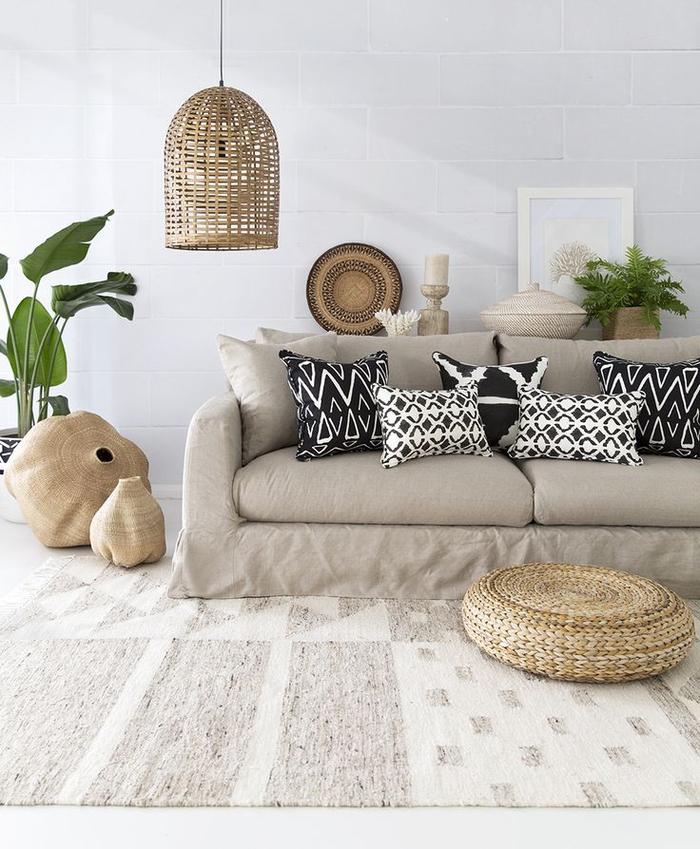 salon élégant de style ethnique chic aux nuances de beige, coussins à motifs ethniques géométriques, suspension en rotin