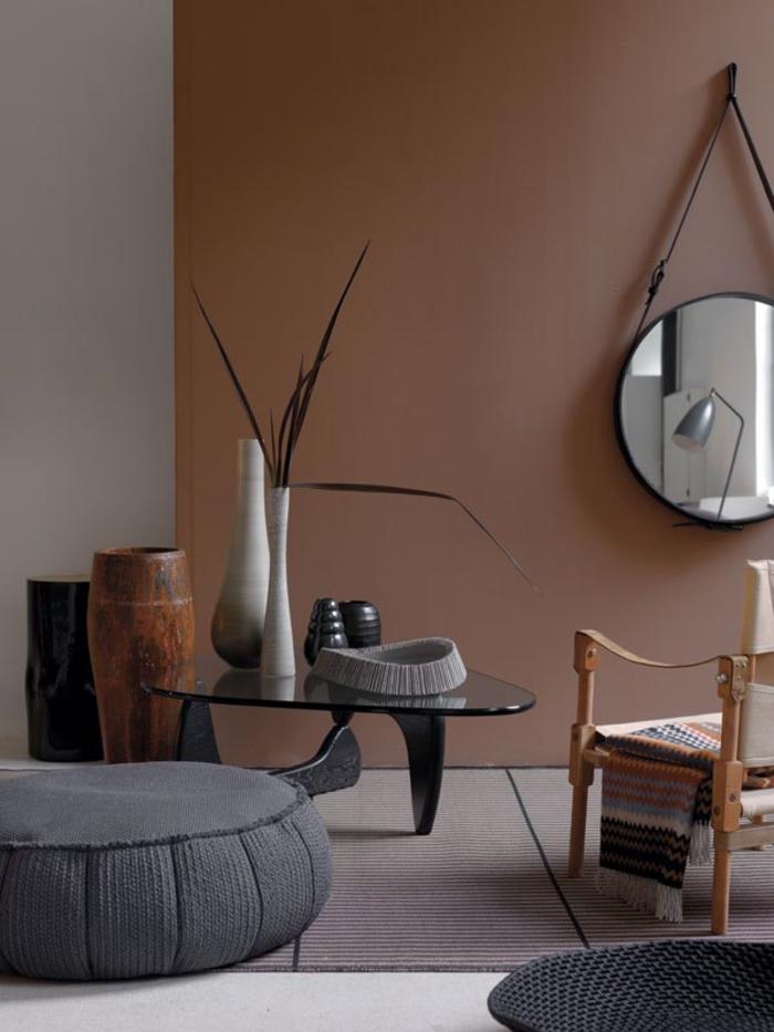 la palette des couleur du salon ethnique chic à inspiration africaine, pouf gris associé à une table élégante en verre noire