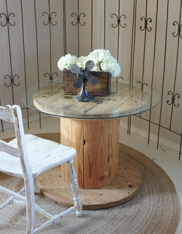 table basse touret avec un plateau en verre, bac en bois, rangement bouquet de fleurs et chaise blanche patinée