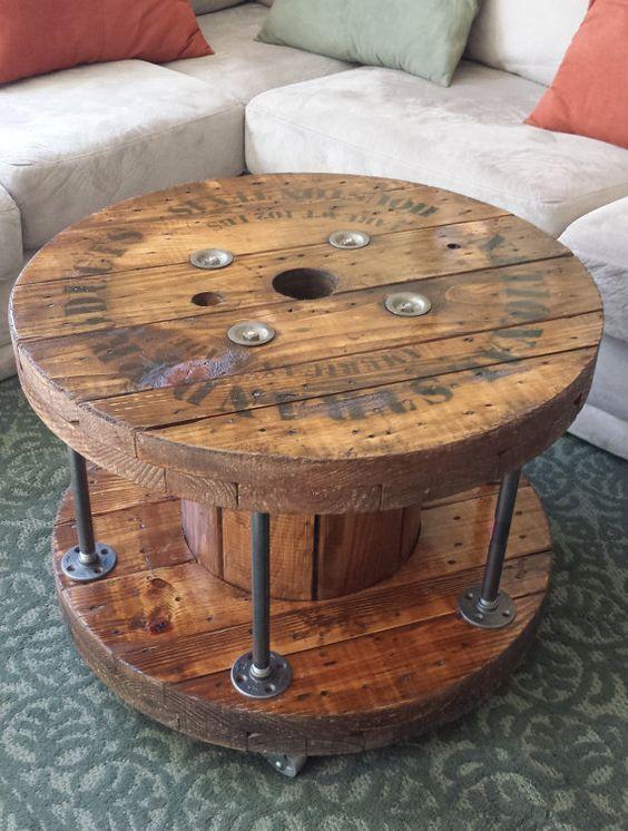table basse touret en bois, avec espace de rangement délimité, tapis vert, canapé blanc cassé et coussins multicolores
