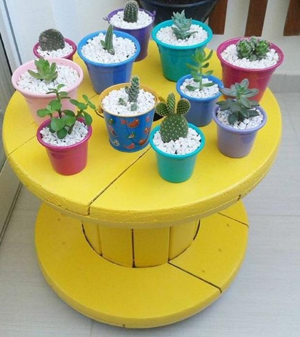 idée de touret tabl basse, repeint en jaune, plantes cactées et succulentts dans des pots de fleurs multicolores, gravier