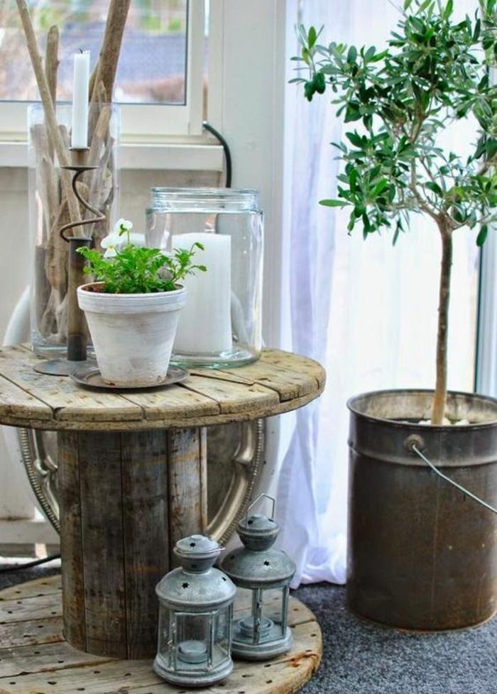 touret bois decoration, table bois brut, lanternes vintage, pot de fleur en terre cuite blanchi, bocal en verre avec bougie à l interieur, arbre planté dans un seau en metal