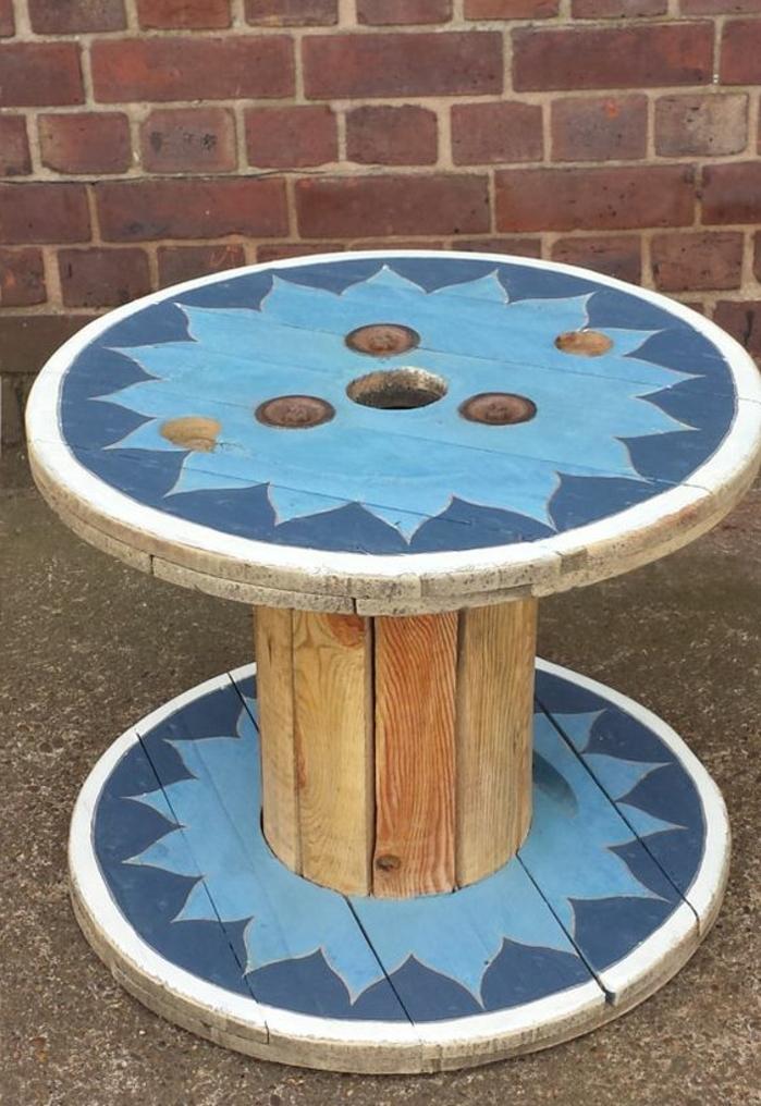 touret deco table basse customisée à la peinture, un motif de fleur bleu clair sur un fond bleu foncé, mur en briques