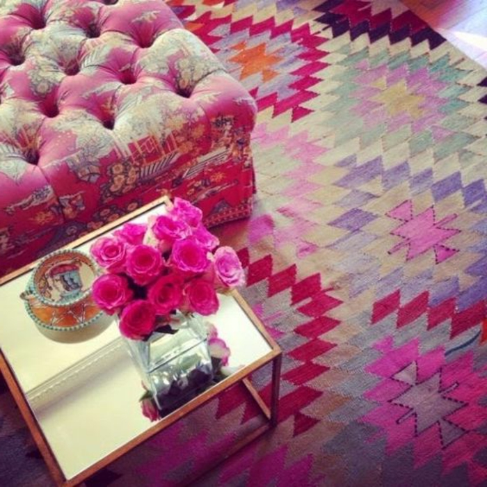 tapis ethnique, imprimés multicolores en rose et lilas, grand pouf rose