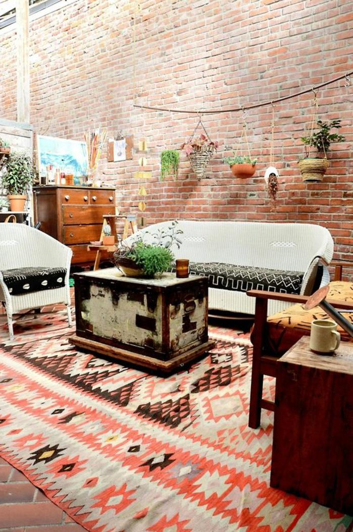 tapis ethnique, mobilier vintage, valise vintage, mur en briques, pots de fleurs suspendus