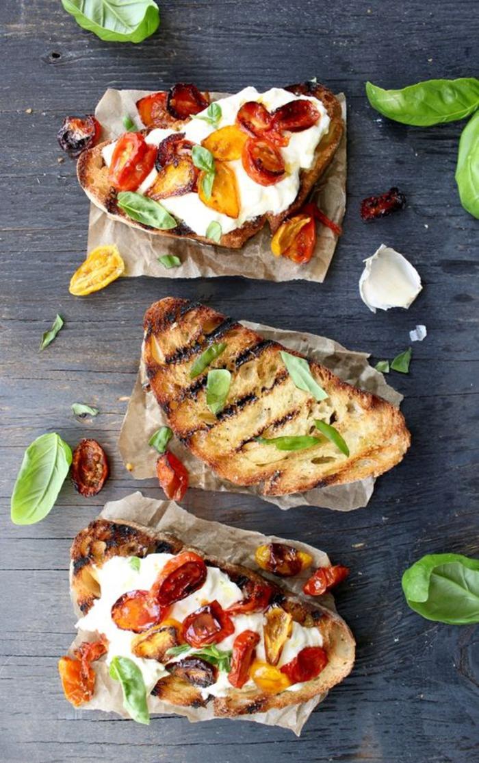 bruschettas croustillantes de pain italien grillé à la buratta, tomates cerises au four et basilic