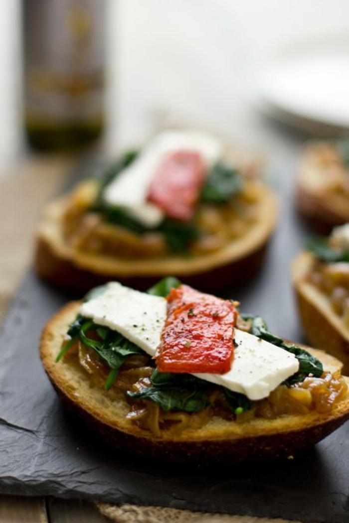 bruschetta végétarienne délicieuse façon sandwich ouvert aux épinards, aux oignons caramélisés et poivrons rôtis