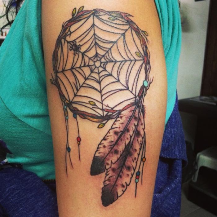 attrape reve tatouage bras, filet toile d'araignée et cerceau en branches d arbre, des plumes en noir et marron, petites perles décoratives