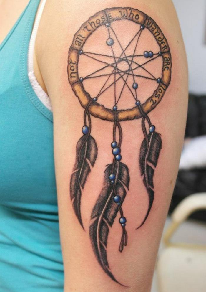 tatouage attrape-rêve, cerceau marron, plumes graphiques, encre noire, perles bleues, filet simple, idée de tatouage femme épaule