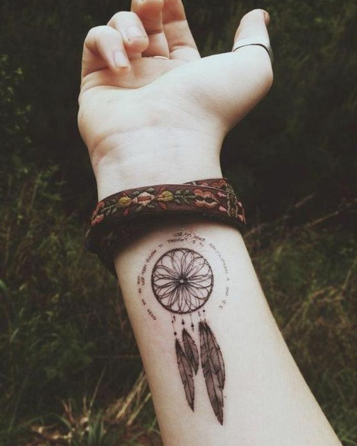 tatouage attrape reve vant bras, rosace et plumes noires, citation en forme ronde, bracelet amérindien aux motifs floraux