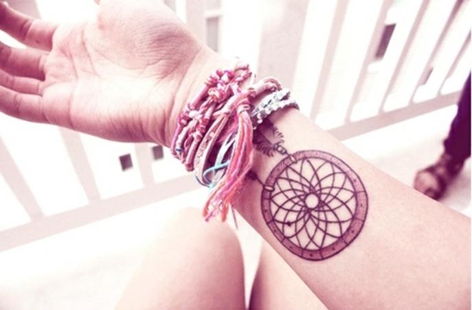 idée de tatouage attrape reve avant bras, cerceau marron, filet noir, bracelets en laine de couleurs diverses