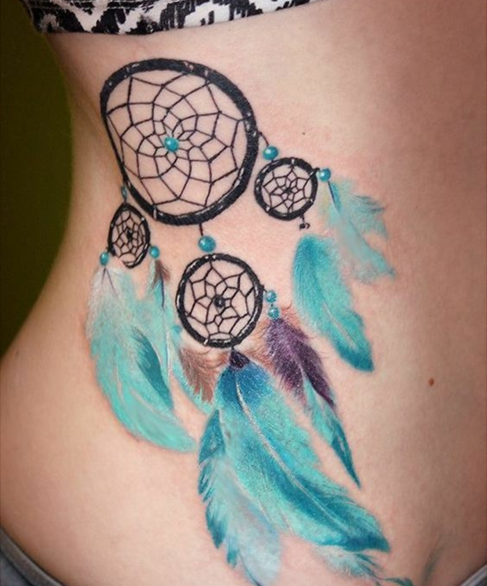 idée de tatouage attrape reve sur les côtes, quatre cerceaux noirs de tailles diverses, perles et plumes bleues, petites touches de couleur mauve et marron