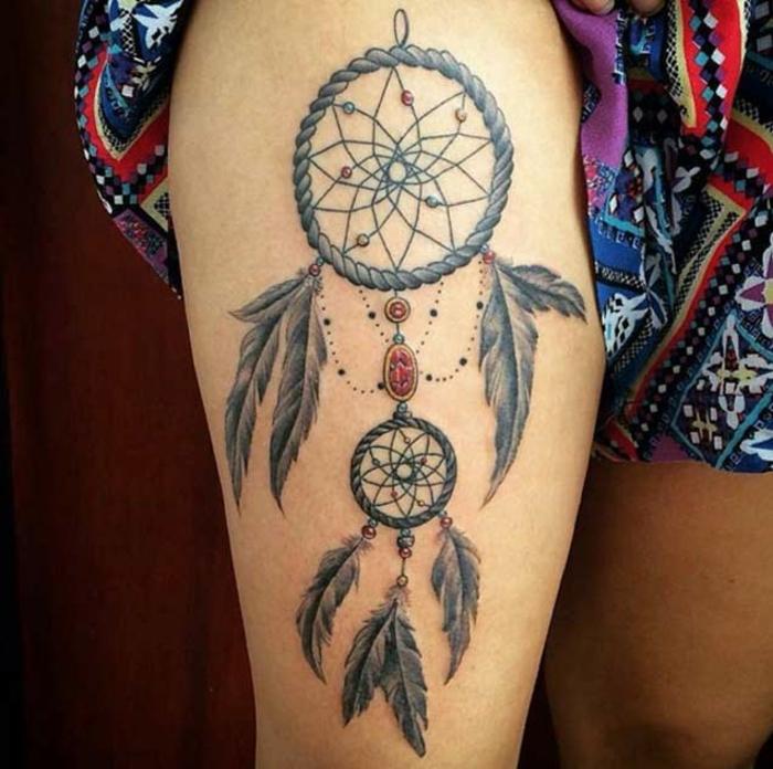 exemple de tatouage attrape reve cuisse, corde cerceau, filet et plumes grises, pierres et perles colorées