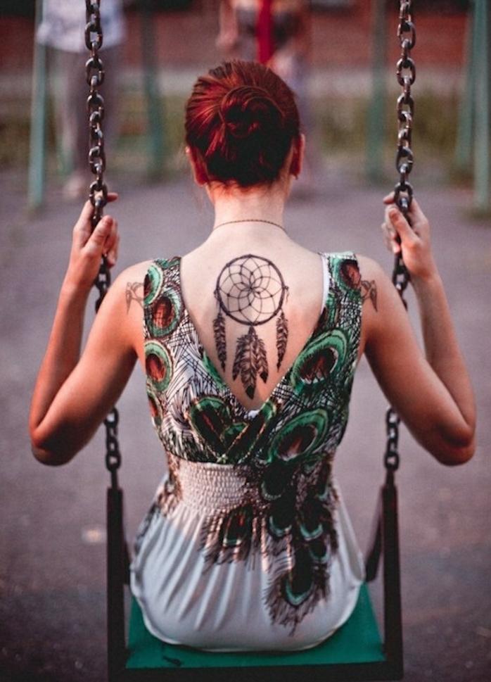 grand tatouage attrape reve sur le dos, cerceau, filet et plumes dessinés à l encre noire, femme aux cheveux rouges