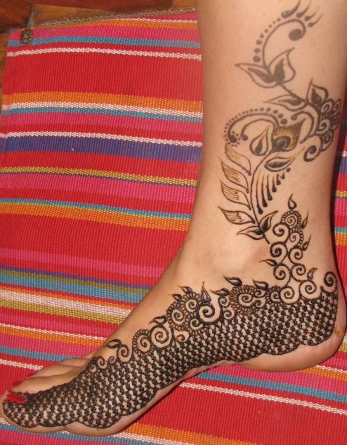 tatouage au henné, coussin ethnique et pied de femme avec dessins au henné