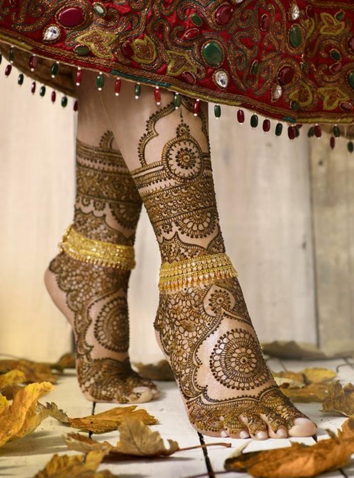 tatouage au henné, grand dessin sur les pieds et robe rouge aux ornements splendides