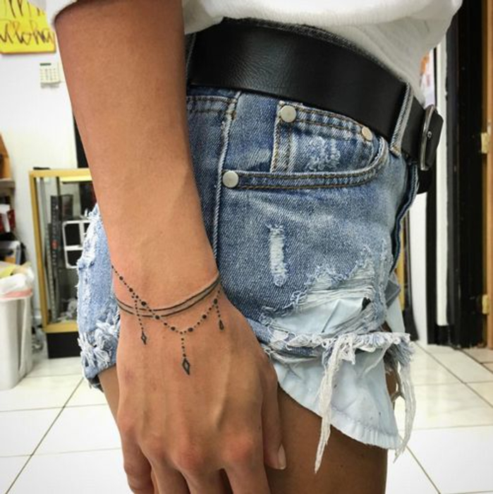 tatouage bracelet, deux fils noirs, chapelet de petites perles et pierres précieuses, idee tatouage femme