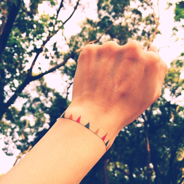 tatouage bracelet poignet, guirlande à fanions, des triangles de couleurs diverses, idee tatouage simple