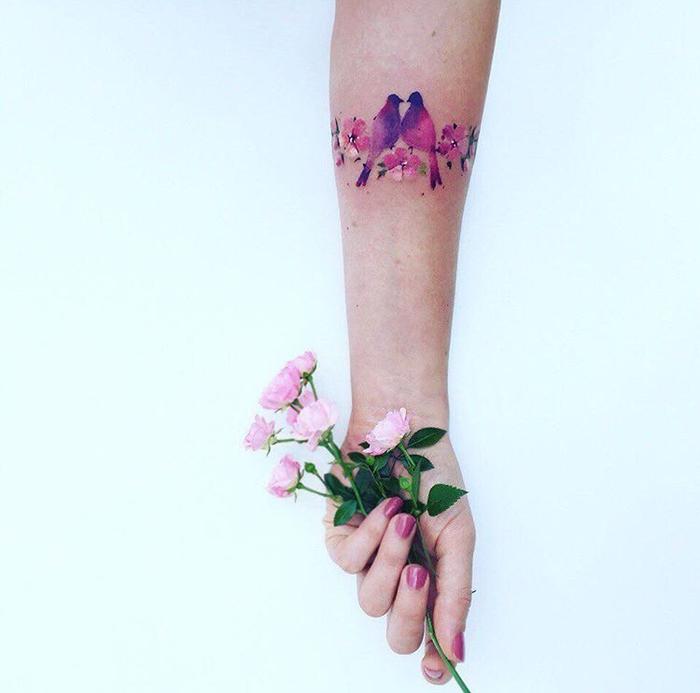 tatouage femme, une branche fleurie, fleurs rose et oiseaux en rose et mauve, idée de tatouage bracelet élégante