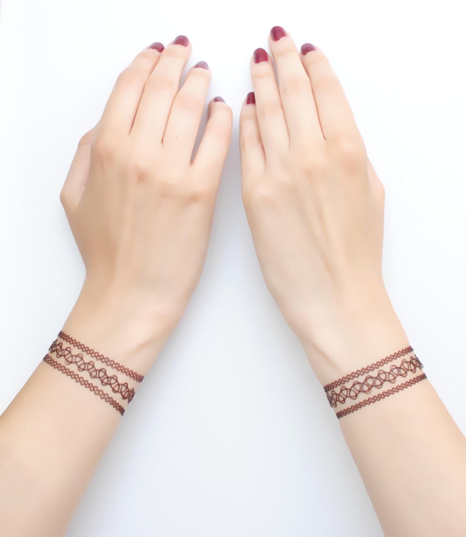 idée de tatouage hénna, tatouage femme au poignet, un réseau rouge, symbolisme caché