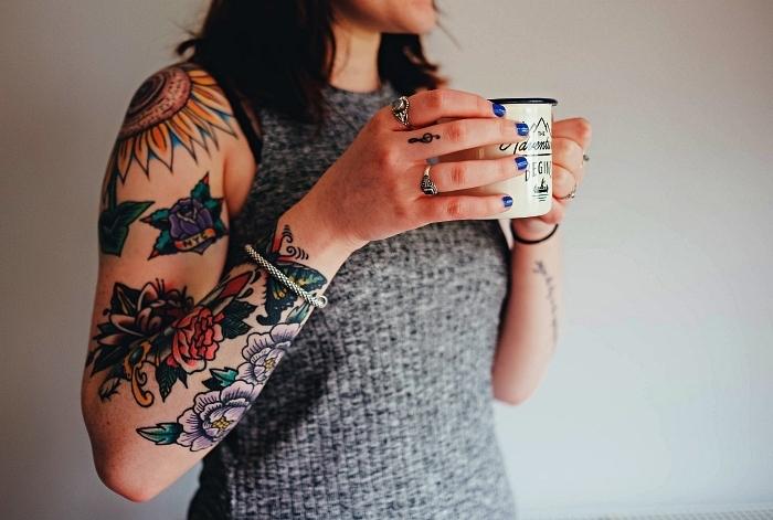 idée de tatouage bras complet à motifs floraux colorés combiné avec un petit tatouage clef de sol, tattoo tournesol à l'épaule