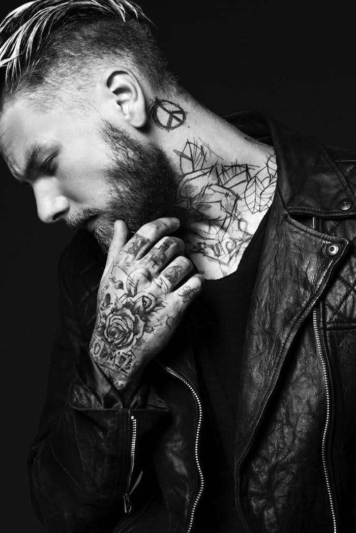 tatouage bras homme, barbe noire, coiffure rasé sur le côté, tatouage sur le cou, veste en cuir noir homme