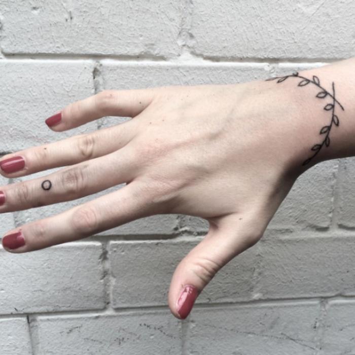 idée de tatouage bracelet poignet pour femme, une branche à feuilles graphique, encre noire