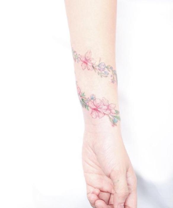 tatouage bracelet femme, une branche fleurie enroulé autour du poignet, fleurs rose, dessin coloré esthétique