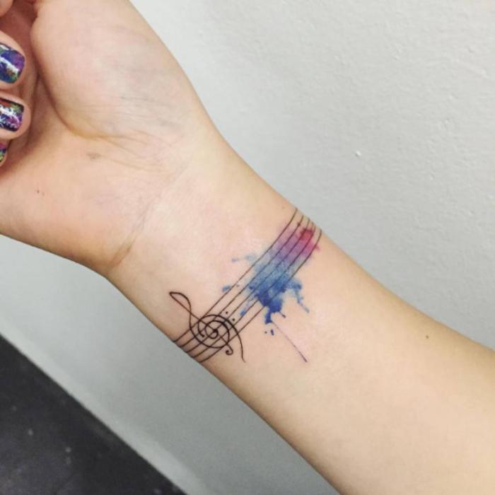 tatouage bracelet sur le poignet, clé de sol et lignes noires, un nuage multicolore en bleu, mauve et rouge