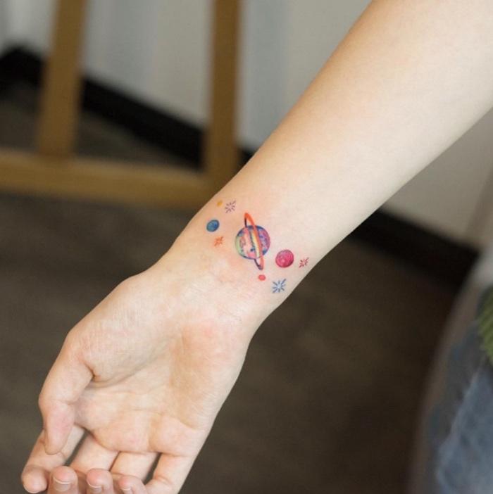 modèle de tatouage femme coloré, les planètes du système solaire, gravitant sur le poignet