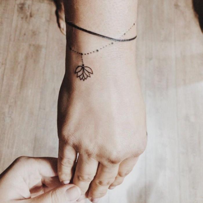 tatouage femme, chapelet de petites perles noires et fleur de lotus, bande noire, idée tatouage poignet