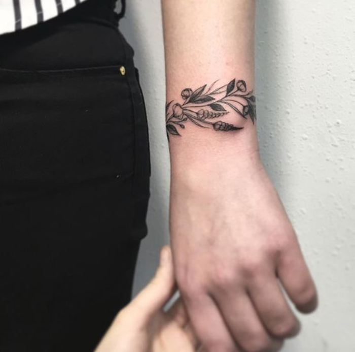 tatouage femme bracelet au poignet, une branche fleurie, dessin encre noire, tatouage feminin