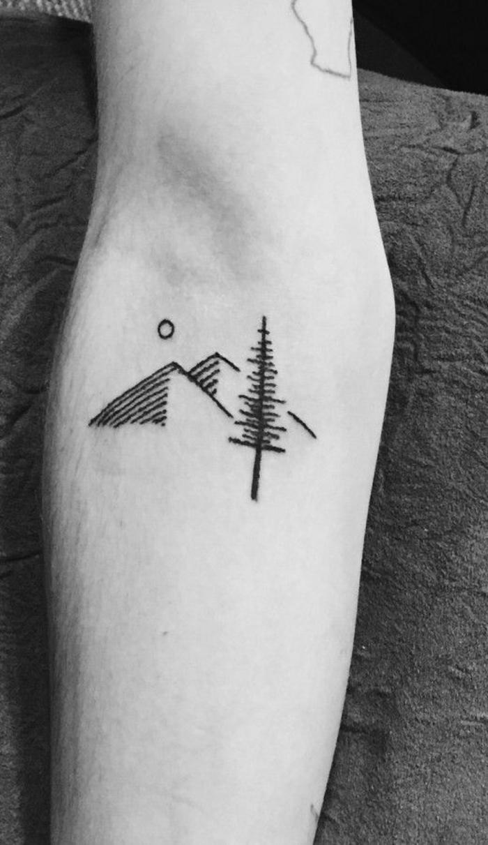 tatouage fin femme, sapin et deux cimes de montagne tatouées près de la coude