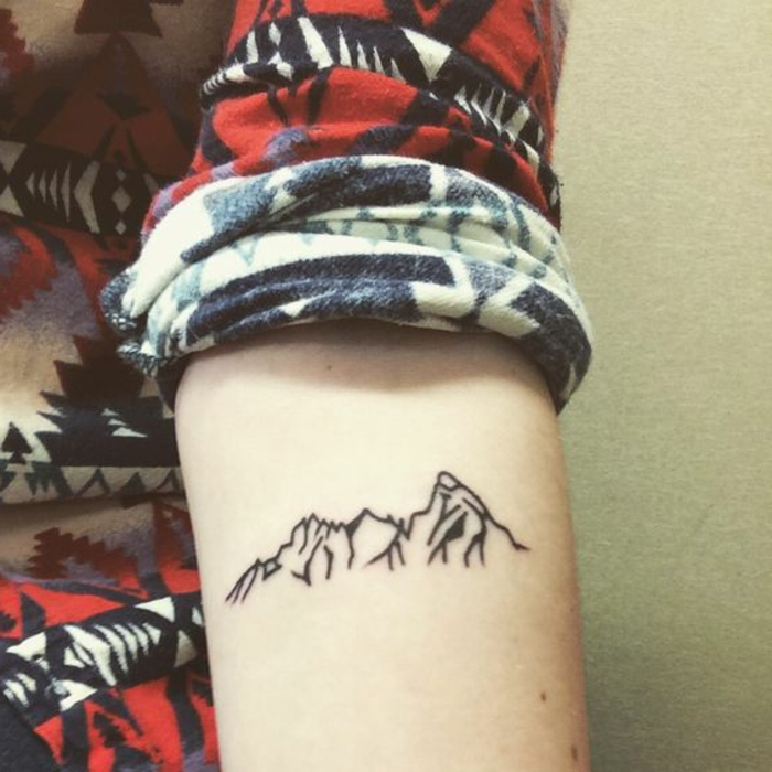 tatouage noir et blanc, montagne sous le bras, chemise multicolore