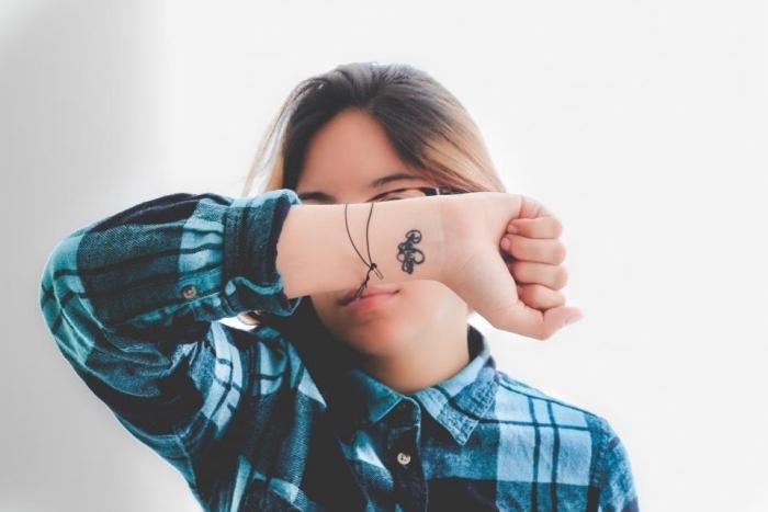 tatouage petit minimaliste, écriture, lettres encre noire sur le poignet, tattoo femme discret