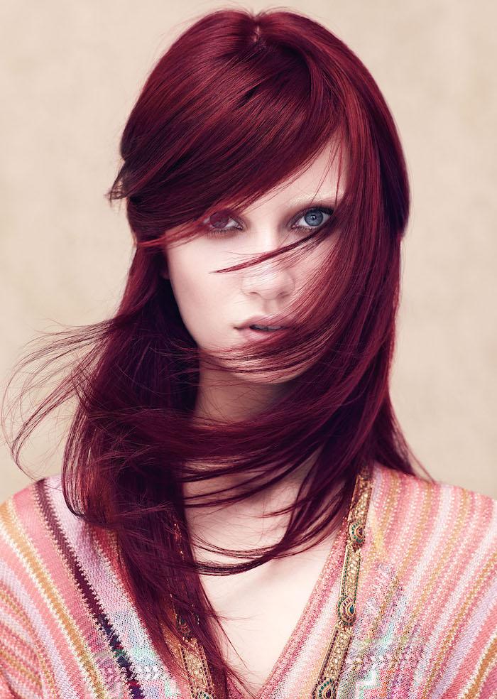 cheveux rouge foncé, coloration bordeaux, coiffure avec frange du côté, robe ethnique en rose et or, cheveux raids