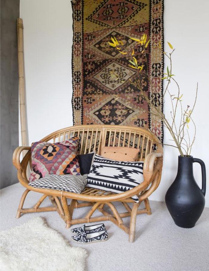 une fauteuil en bambou décorée de coussins de style ethnique chic, tenture ethnique chic comme une décoration murale originale