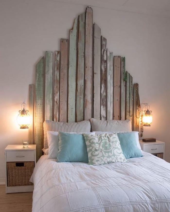 fabriquer une tete de lit en planches de bois brut, aspect usé, linge de lit blanc, bleu et beige, parquet clair, lanternes vintage en guise de lampe de nuit