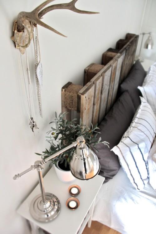 faire une tete de lit en palette de bois brut, idée deco chambre a coucher rustique, coussins gris et blancs, linge de lit blanc, bois de cerf deco murale