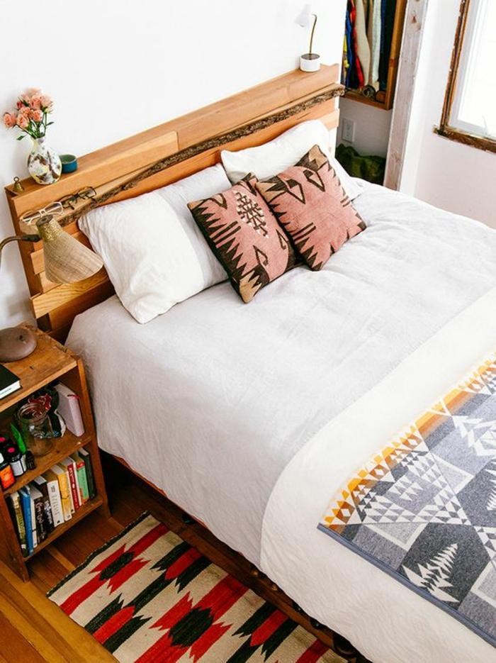 déco de chambre avec tissu ethnique, coussins aztèques en rose et noir, chevet avec livres