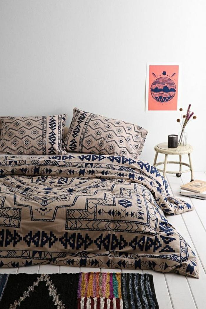 tissu ethnique sur le lit, sol en planches de bois, petit chevet sur roulettes, carpette exotique