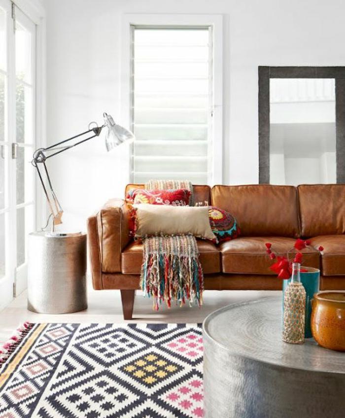 tissu ethnique, salon style boho chic, sofa en cuir, lampe de sol, table métalliqye ronde