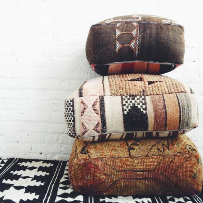 tissus ethniques, coussins ethniques en forme carrée, carpette en noir et blanc, miur en briques blanches