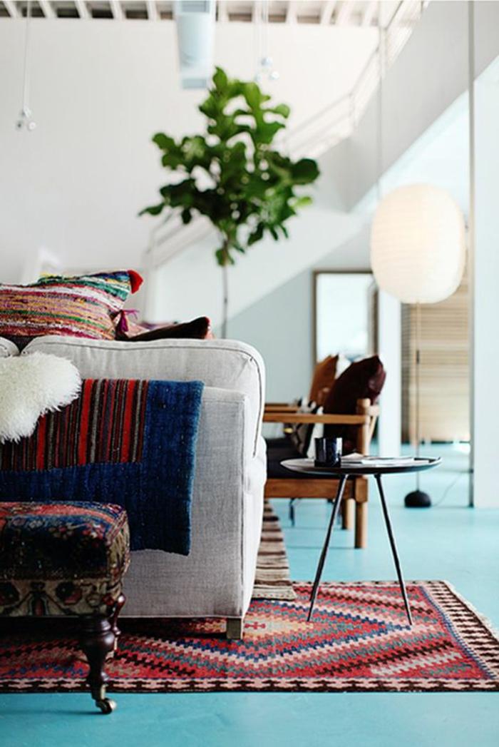 tissus ethniques, sol bleu, tapis aztèque, arbre vert, sofa gris pâle, enduit blanc