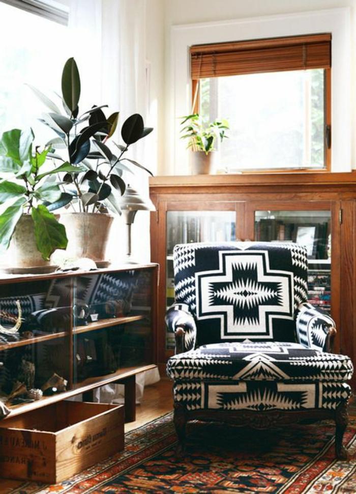 fauteuil décoré de tissu ethnique, buffet en bois avec vitrine, étagère vitrée et plantes vertes