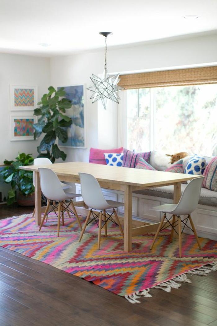 tissus ethniques, tapis géométrique, grande table en bois clair, chaises scandinaves