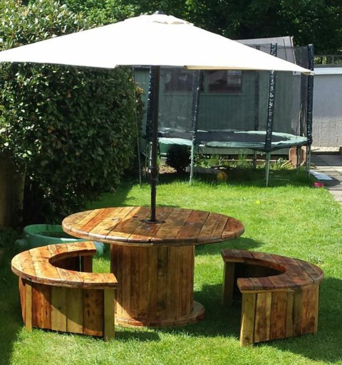 amenagement jardin récup, deco touret table et bancs en bois, demi cercle, un parasol qui passe par le centre, gazon vert